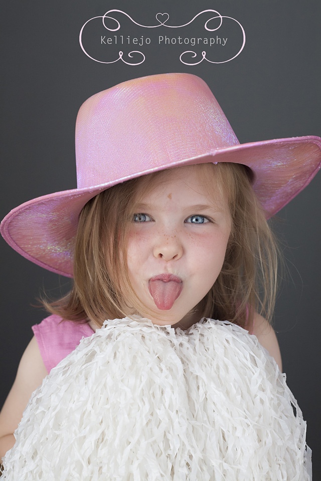 Cheshire children's photography  of a little girl dressed up in a pink hat with  white pompoms from a Photo Booth