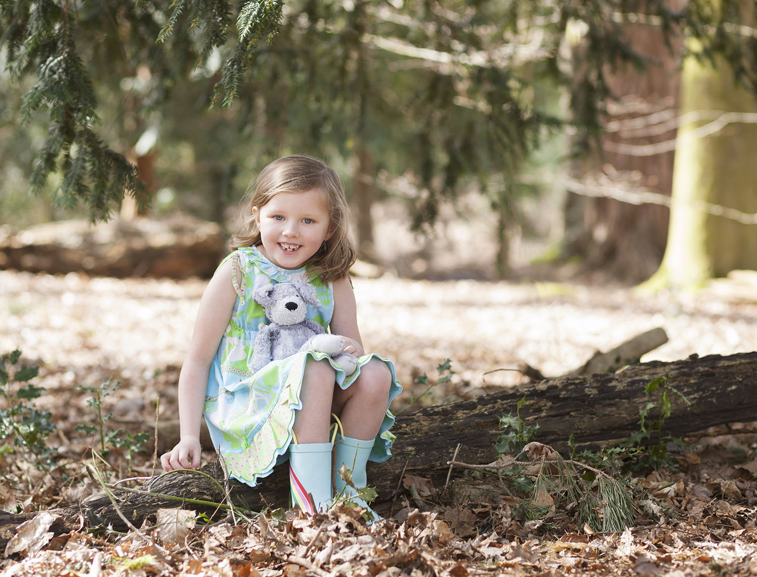 Girl with teddy bear sat on a log during Spring mini shoot in Styal Woods in Manchester