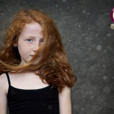 Cheshire children's photography of a young girl with red hair blowing across her face.