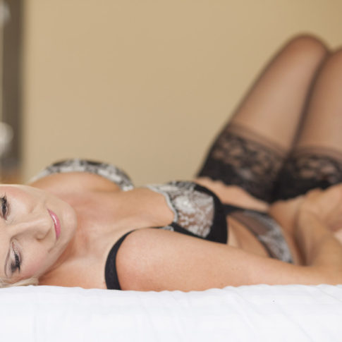 Cheshire boudoir photography of a lady lay on a bed in a hotel room with lingerie on.