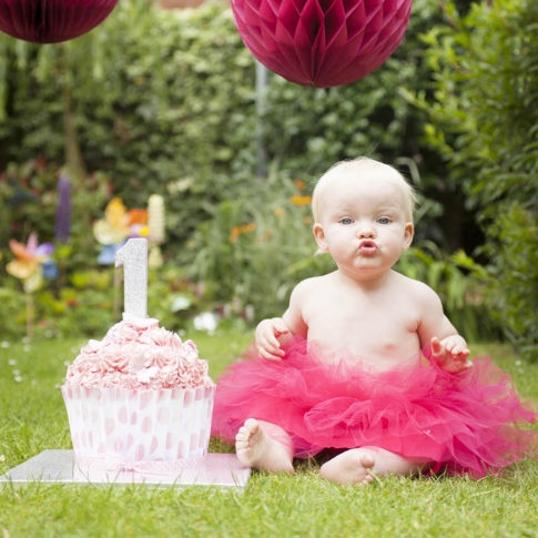 Cheshire cake smash photography of a one year old baby in a pink tutu next to a birthday cake with a number one on it.