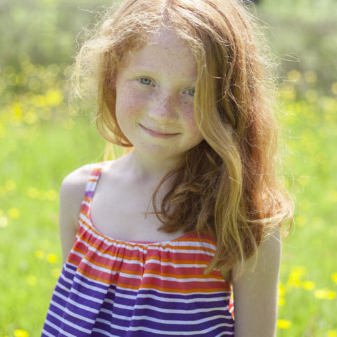 Cheshire children's photography of a ginger haired little girl in a field at Abney Hall Park.