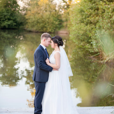 Cheshire wedding photography of a bride and groom by the lake at Styal Lodge wedding venue.