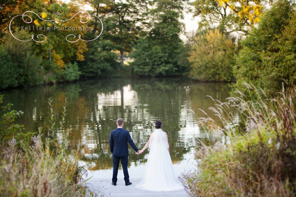 Styal Lodge wedding photography of the bride and groom holding hands at the lake.