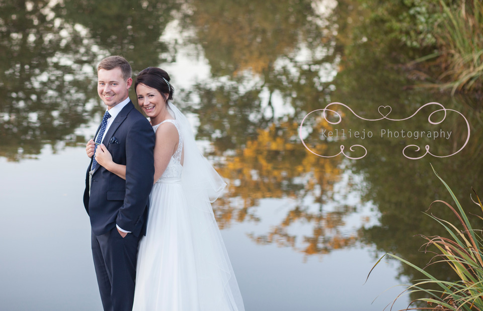 Styal Lodge wedding photography of the bride and groom hugging at the lake.