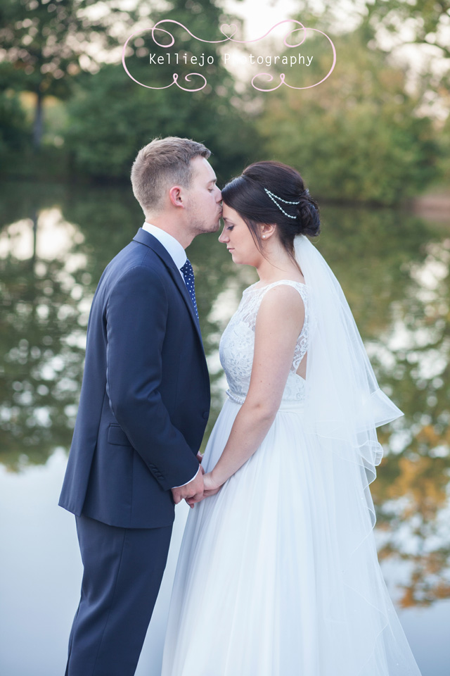 Styal Lodge wedding photography of the groom kissing the brides forehead.