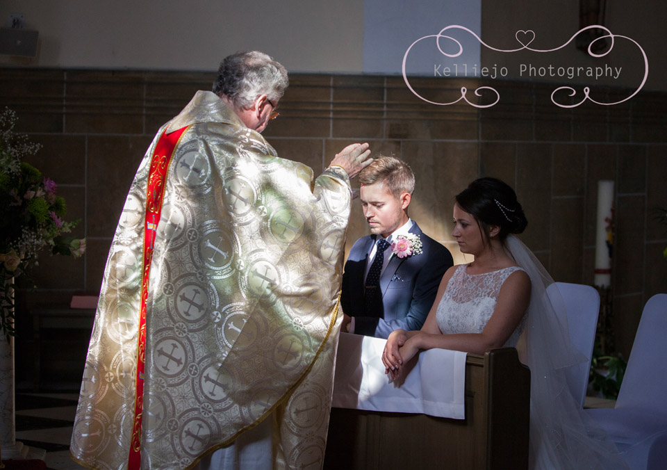 Styal Lodge wedding photography of the Catholic priest blessing the bride and groom.