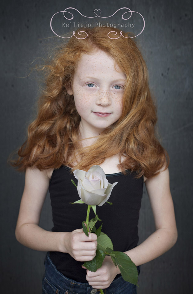 Children's photography of a red haired little girl holding white rose.