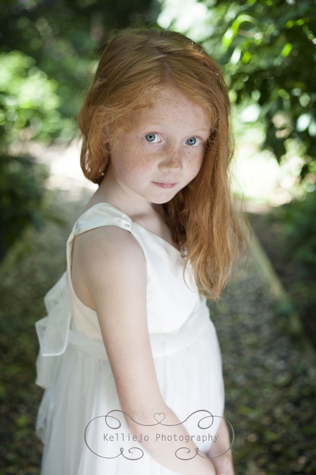 Children's photography of a red haired little girl wearing a white dress at Abney Hall Park.