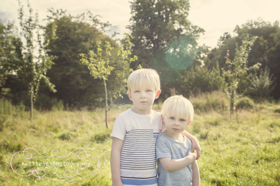 A photograph of two brothers hugging and looking in the camera on a sunny day at Abney Hall Park