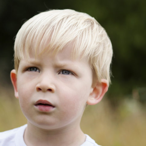 Children's photography of a young boy looking thoughtfully into the distance.