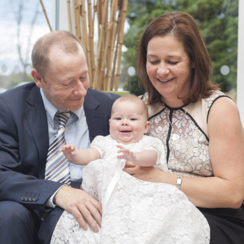 Family photography of a Mum and Dad holding a baby wearing a christening gown.