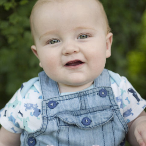 Children's photography of a young baby dressed in denim dungarees smiling directly at the camera.