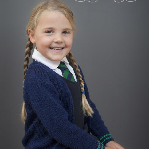 A school photograph of a primary school girl but long plaits and a big smile
