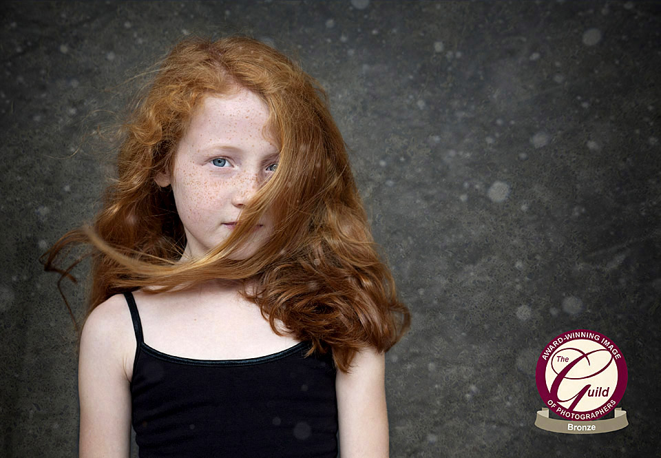 Children's photography of an award winning photograph of a red haired ginger girl with her hair blowing across her face on a snowy background.