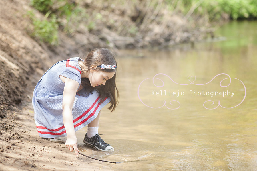 Portrait of a little girl playing in a stream in Styal in Wilmslow