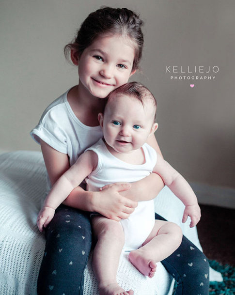 older sister holding younger brother
